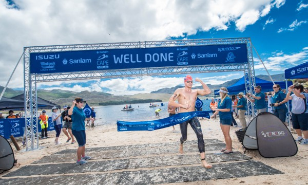 Danie Marais claimed gold at the inaugural Sanlam Cape Mile at the picturesque Eikenhof Dam (Grabouw Country Club, Western Cape) on Saturday, 14 February 2015.  Marais completed the swim in a well-deserved time of 17 minutes 41 seconds.  Seen here:  An ecstatic Danie Marais crosses the finish line.  PHOTO CREDIT:  Volume Photography