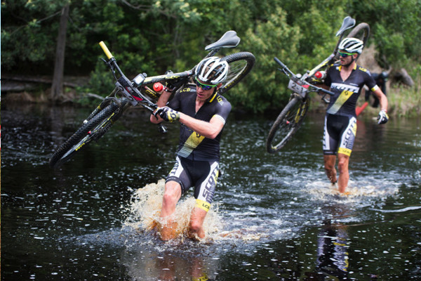 Matthys Beukes (front) and Gert Heyns of SCOTT Factory Racing LCB 2 opt to portage through a river on their way to winning Stage 1 of the Cape Pioneer Trek from Mossel Bay to George, South Africa on Monday. Photo credit: Zoon Cronje/Nikon
