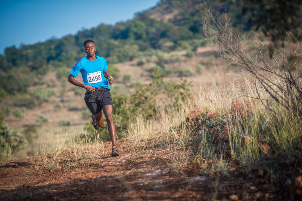 Givemore Mudzinganyama claimed gold in the men's 24km FNB Platinum Trail Run at the ATKV Buffelspoort on Sunday, 22 May 2016.  Mudzinganyama completed the 24km route in an impressive time of 01 hour 25 minutes 19 seconds.  Seen here:   Givemore Mudzinganyama in action on the day.  Photo Credit:  Tobias Ginsberg