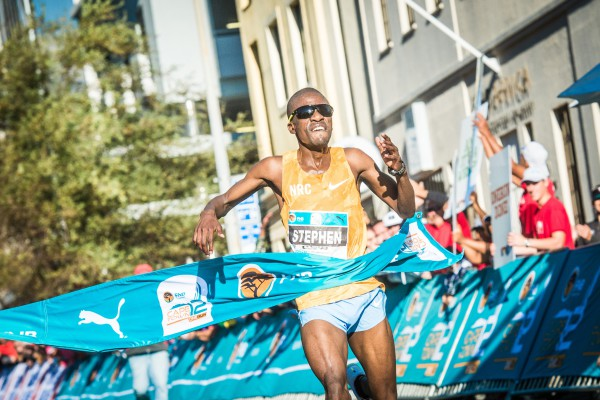 In his 12km debut, South Africa's Stephen Mokoka showed the international contingent and the top three from 2015, Emmanuel Bett, Daniel Salel and Timothy Toroitich, a clean pair of heals at the 2016 FNB Cape Town 12 ONERUN that took place in the Mother City today (Sunday, 15 May 2016).  Seen here:  Mokoka claiming victory in Bree Street Cape Town in an impressive time of 33 minutes 34 seconds.  Photo Credit:  Tobias Ginsberg