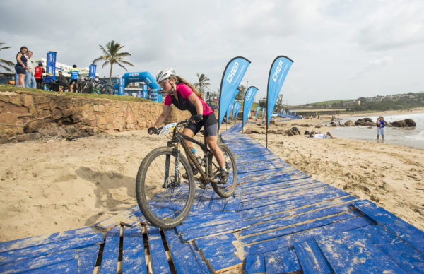 Scottburgh local, Candice Parker-Dennison charges onto the sand and Scottburgh Main Beach as she claims victory in the women's race of the 2016 Sappi Scottburgh MTB Race, the third leg of the South Coast MTB Series. Anthony Grote/ Gameplan Media