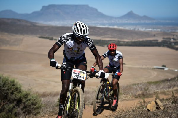 Thando Klaas leads teammate Lorenzo Leroux up a climb during the Prologue of the 2017 Absa Cape Epic. Photo by Sportograf.