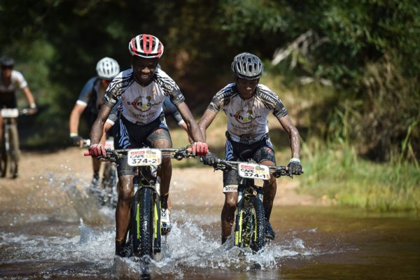 Lwazi Ntsakaza (left) and Theo Ngubane (right) cross a river during the 2017 Absa Cape Epic. Photo by Sportograf.