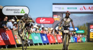 Theo Ngubane wheelies across the final finish line of the 2017 Absa Cape Epic alongside his Songo-Investec 2 teammate Lwazi Ntsakaza. Photo by Sportograf.