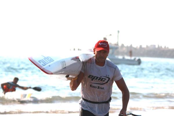 Hank McGregor runs up the beach to win the Bay Union Open Ocean Challenge Surfski Challenge  the first leg of the Bay Union Open Ocean Surfski Challenge series. Lynne Hauptfleisch/ Gameplan Media