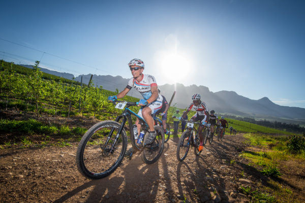 """It was a warm start to Stage One of the 2017 FNB Wines2Whales Mountain Bike (MTB) Ride at the picturesque Lourensford Wine Estate on Monday, 30 October 2017.  The first of two destination stages, Stage One saw riders having to complete a 64km route that featured a 1650m ascent before crossing the finish line at Oak Valley Wine Estate (Elgin-Grabouw), their home away from home.  Olympian Phetetso Monese (Lesotho) and Leonhard Lukoschek (Germany) of Team ACE Lesotho applied pressure from the start.  """"This is my third W2W,"""" says Monese.  """"Last year I finished first in the men's race.  I really want to defend my title.  So we went fast from the start.  Stage One featured some great riding.  I was a little worried when I heard that Leonhard was a roadie, but after today I'm no longer worried.""""  Seen here:  Team ACE Lesotho's Leonhard Lukoschek and Phetetso Monese leading the field during Stage One of the FNB Wines2Whales MTB Ride.  Photo Credit:  Tobias Ginsberg"""