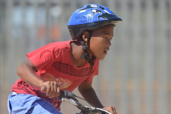 """By taking part in the 2017 BUCO Origin Of Trails Two-Day MTB Stage Race on Saturday, 25 November 2017 and Sunday, 26 November 2017, riders will make a difference in the lives of the children of the Aitsa After Care Centre.  """"The Aitsa After Care Centre opened its doors in January 2014,"""" says Marietjie Steyn, Aitsa After Care Centre Founder and Manager.  """"The Centre strives to expose children to fun activities and programs in an alternative home environment where they feel loved and special.  We currently have 145 children between the ages of 5 and 9.  All the children reside in the Dwarsriver Valley, Kylemore in the Banhoek Valley and surrounding farms.  We offer meals, sport, chess, choir, drama, e-learning, mathematics, reading programs, homework assistance, counselling, parent support groups and life skills training to name just a few.""""  Seen here:  Zandre Swarts enjoying being outdoors on his bicycle."""