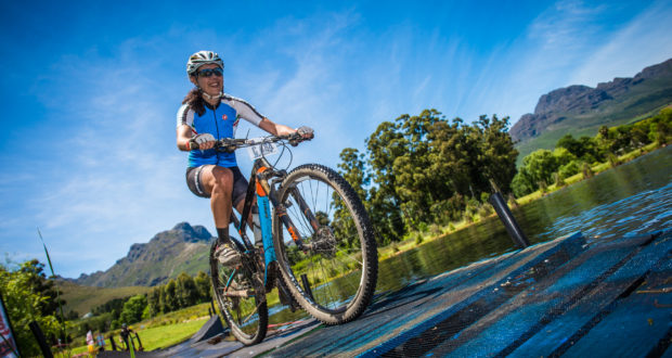 Stage Two of the Origin Of Trails MTB Experience Short Route will start and finish at Coetzenburg Sports Fields (Stellenbosch) on Sunday, 25 November 2018 and feature a +- 27km memorable MTB experience that includes a 550m vertical ascent.  Seen here:  Janine Moore enjoying the floating bridge at Mont Marie during the 2017 event.  Photo Credit:  Tobias Ginsberg