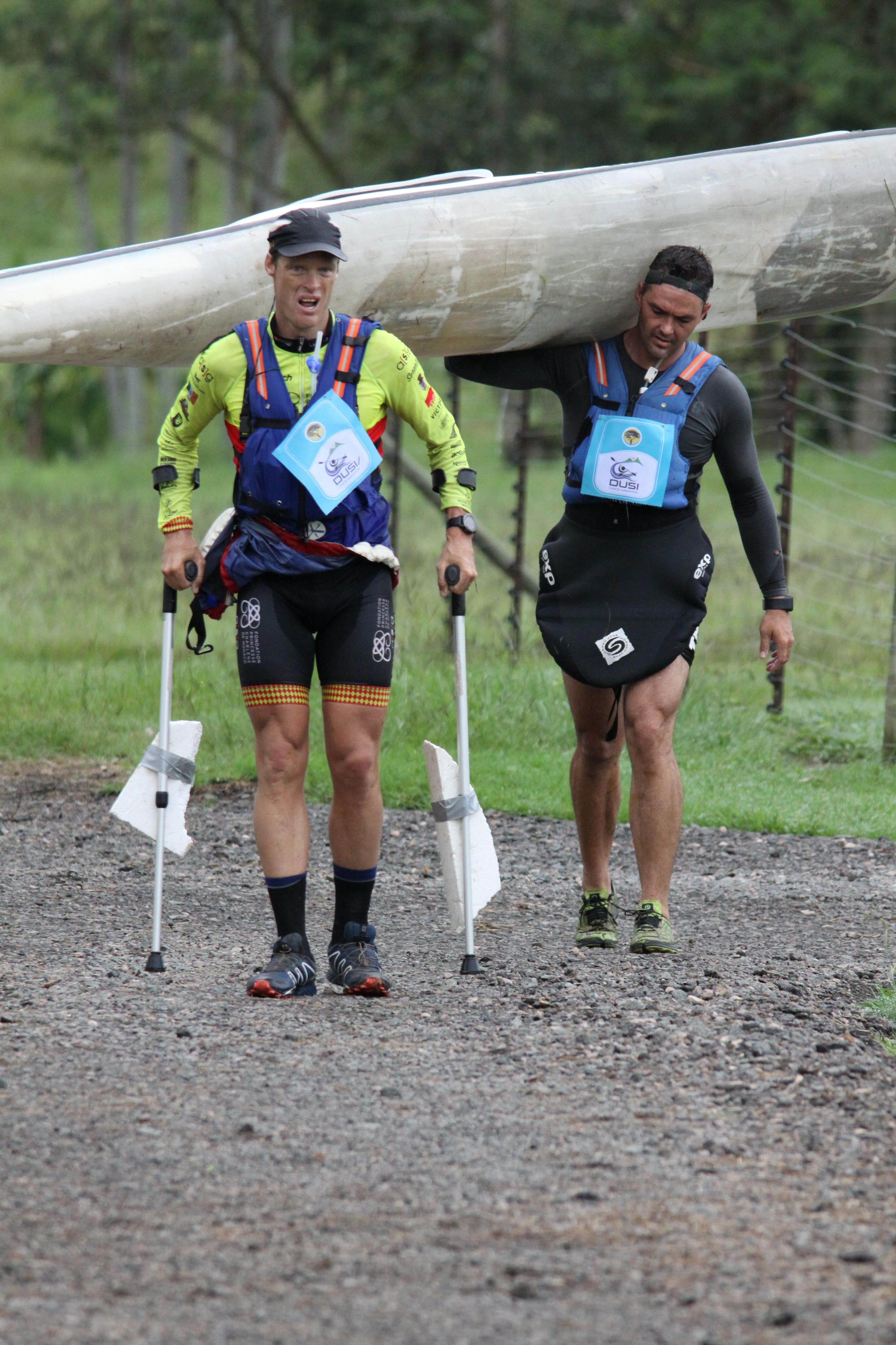 Deaf Olympic star Terence Parkin struggling on crutches on a portage on the first day of the FNB Dusi while his K2 partner Mark Mulder carries their boat on his own. Jason Parker/ Gameplan Media