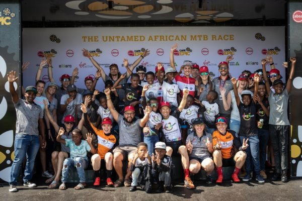 Annika Langvad, Anna van der Breggen, Christoph Sauser, Simon Andreassen Ntlantla Nonkasa and Lwazi Ntsakaza celebrate completing the 2019 Absa Cape Epic with the Investec-songo-Specialized support crew and a few of the songo.info children who came out to cheer them on at Val de Vie. Photo by Michal Červený.