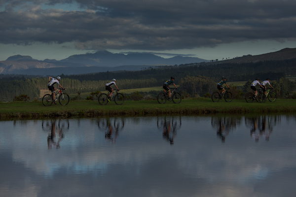 Riders pass by a damduring stage 1 of the 2019 Absa Cape Epic Mountain Bike stage race held from Hermanus High School in Hermanus, South Africa on the 18th March 2019. Photo by Dwayne Senior/Cape Epic PLEASE ENSURE THE APPROPRIATE CREDIT IS GIVEN TO THE PHOTOGRAPHER AND ABSA CAPE EPIC