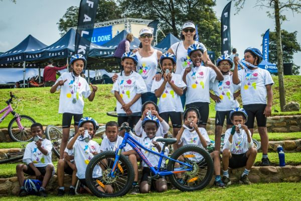 Seen here (back from left to right):  Marleen Lourens and Bianca Grobbelaar (Aitsa! Cycling Initiative Co-ordinator /  Marketing Portfolio) with the children from the Aitsa! Aftercare Centre at the 2018 Fedhealth MTB Challenge.  Photo Credit:  Tobias Ginsberg